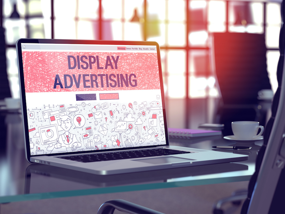 A computer showing a display ad sits on a desk.