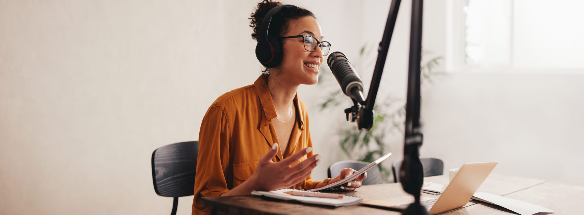 Woman recording a podcast on her laptop computer with headphones and a microphone.
