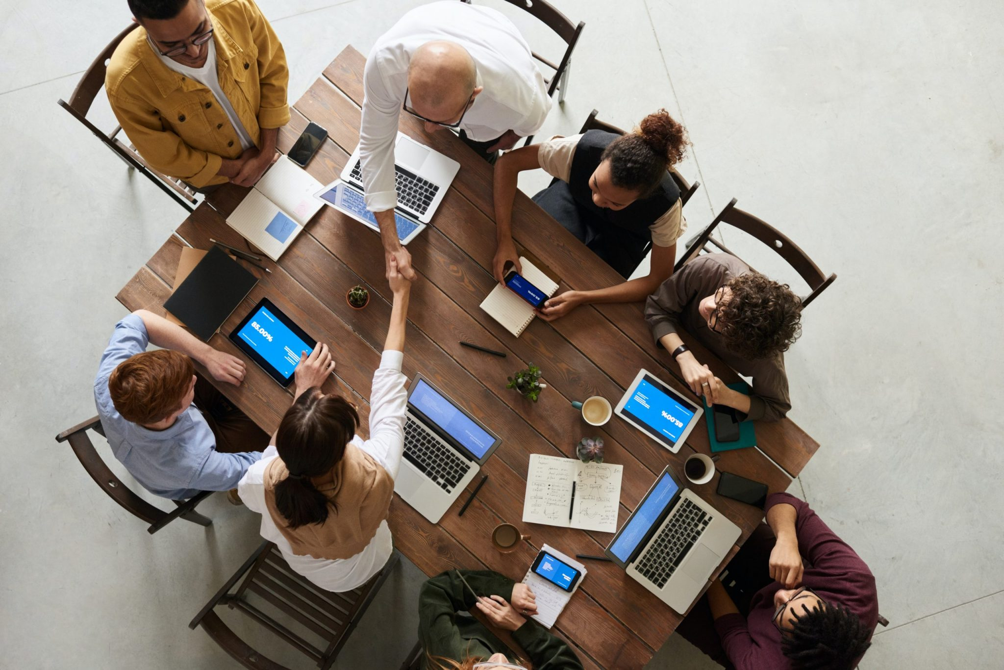 people in a meeting with different devices
